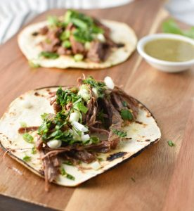 Shredded steak tacos on a wooden board