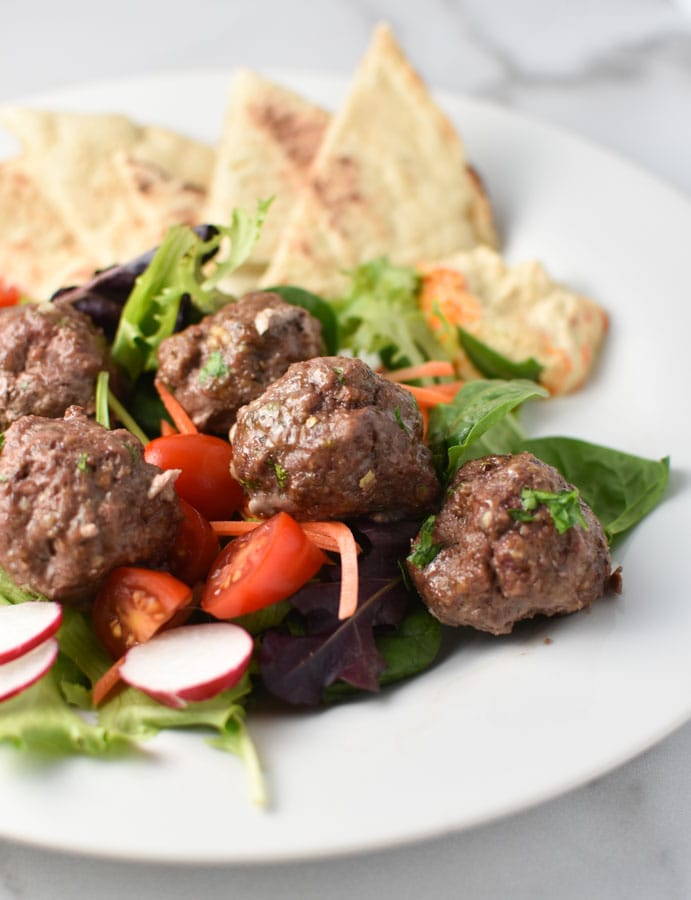 meatballs in a greek salad with pita and hummus on a white plate