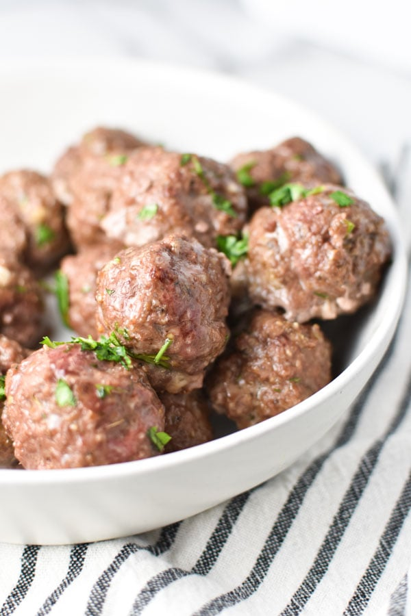meatballs in a large white bowl topped with parsley