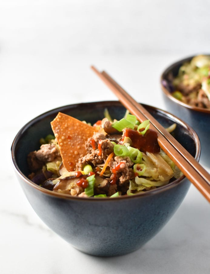 an egg roll bowl with a wonton chip and sriracha on top with chopsticks