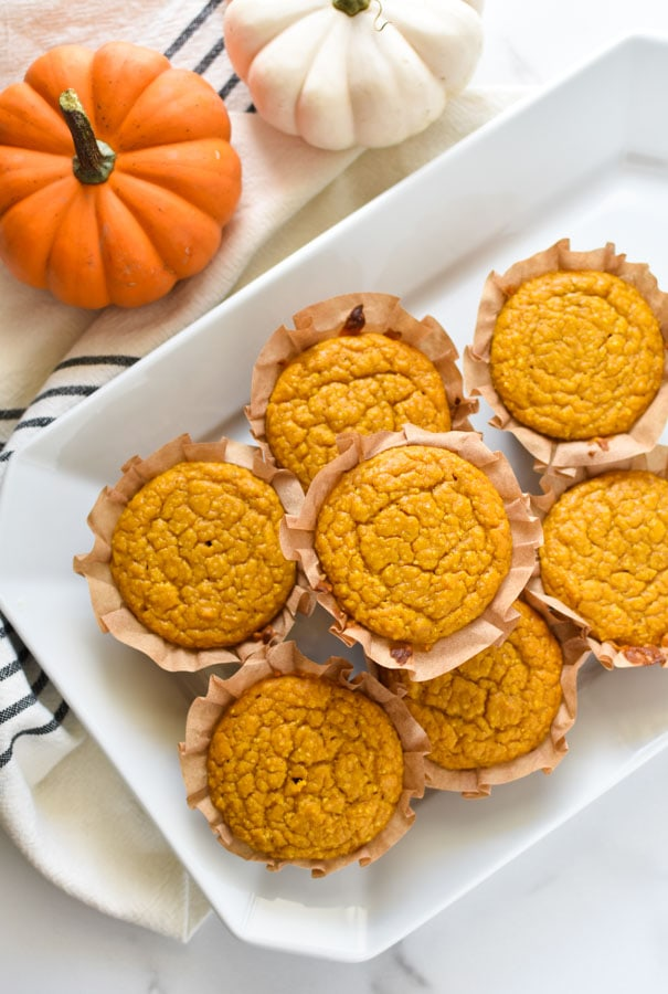 pumpkin cornbread muffins stacked on a white plate next two two pumpkins