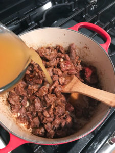 pouring broth into texas chili