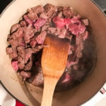 stirring a big pot of meat on the stove