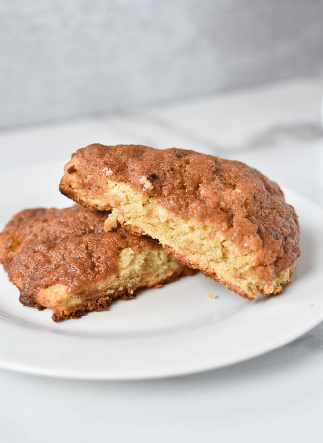 two cinnamon scones stacked on top of each other on a white plate