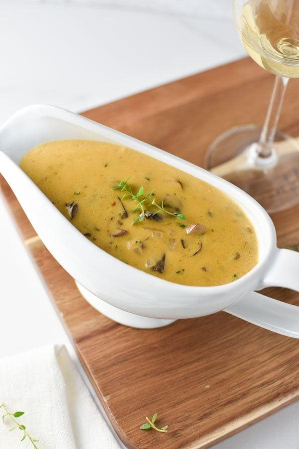 mushroom gravy in a white bowl on a wooden board