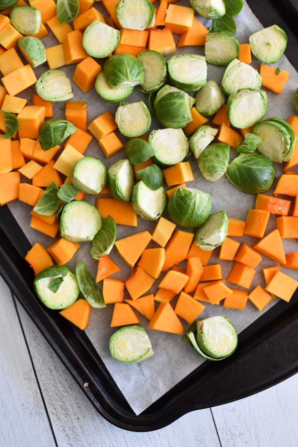brussels sprouts and butternut squash on a roasting pan