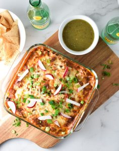 Enchilada casserole on a cutting board with chips, salsa, and topo chico alongside chopped green onions