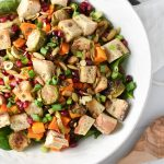Roasted Winter Panzanella salad in a white bowl with tongs