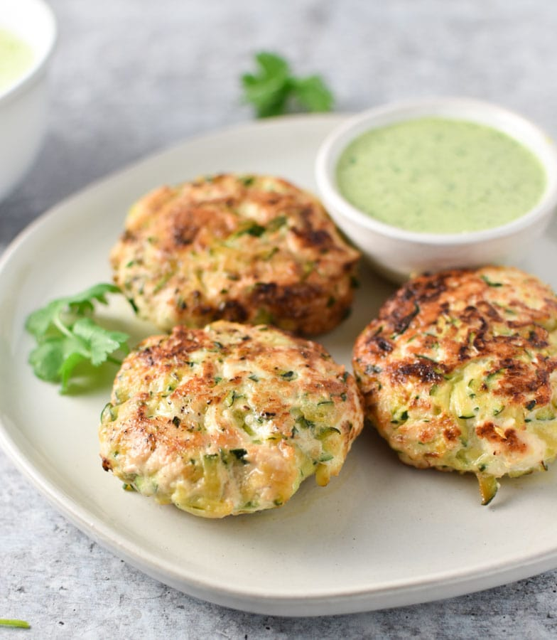 Plain chicken zucchini poppers with a creamy cilantro sauce in a bowl on a concrete surface