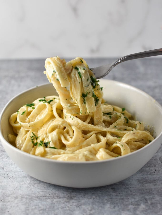 Fettuccine pasta wrapped around a fork that's lifted above a big white bowl of pasta. Parsley is sprinkled on top.