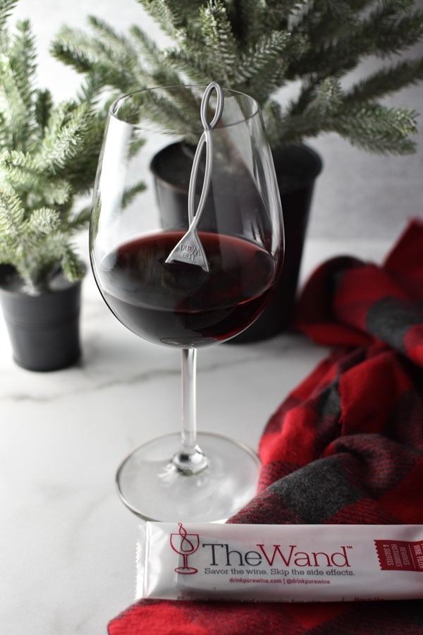 A glass of red wine in front of two small Christmas trees