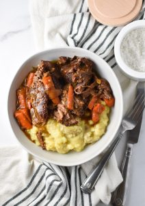 Pot roast, carrots, and mashed potatoes in a bowl on top of a striped towel with a knife and fork to the side