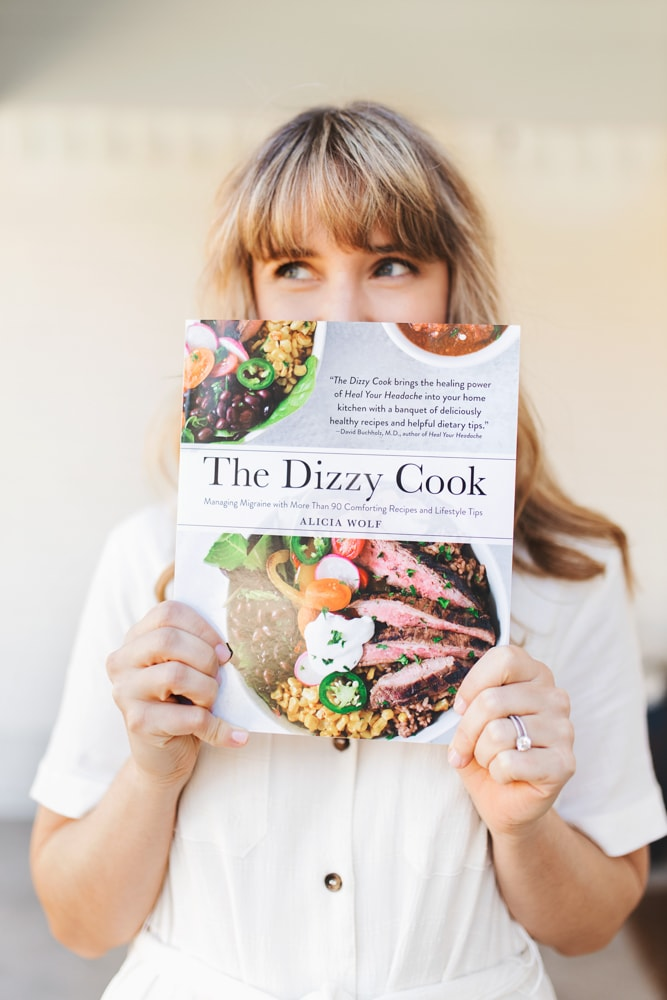 A girl holding The Dizzy Cook Cookbook in a white dress