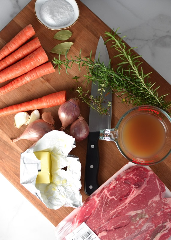 Carrots, shallots, butter, meat, broth, and herbs on a cutting board