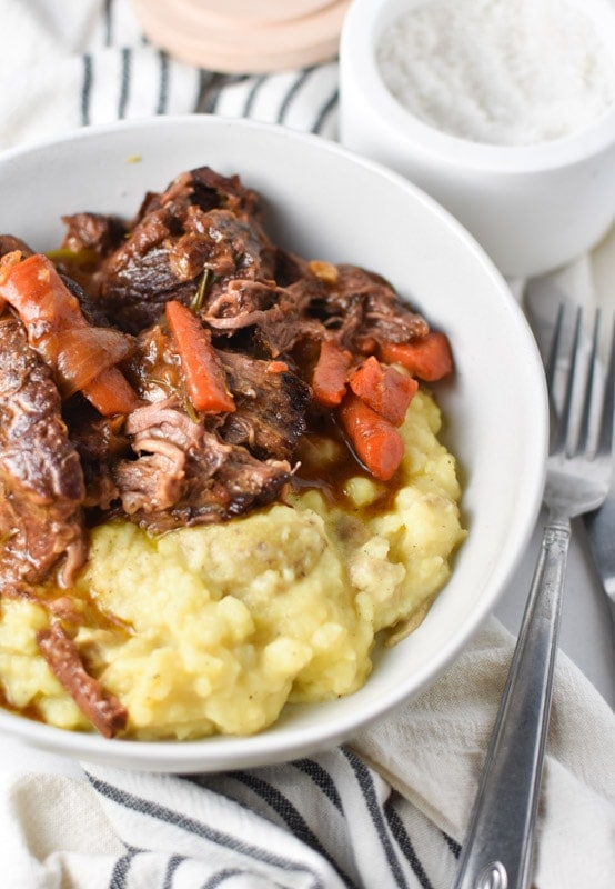 Dutch oven pot roast in a white bowl with mashed potatoes and salt