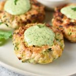 Three chicken zucchini bites with creamy cilantro sauce on the tops and a sprinkle of parsley