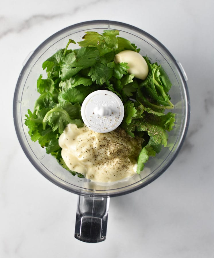 Ingredients for cilantro cream sauce in a food processor