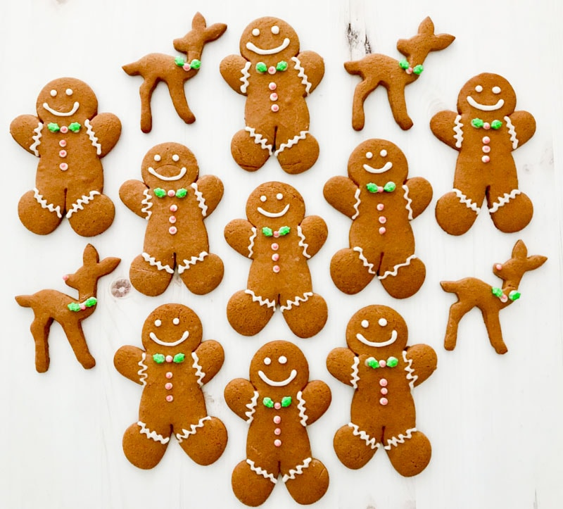 Decorated gingerbread men all lined up next to each other with gingerbread deer