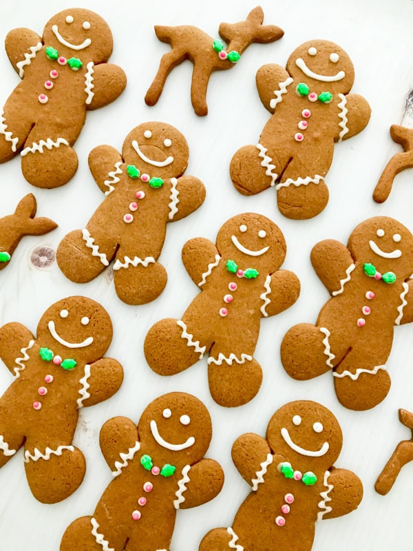 Gingerbread men with green bow ties and pink buttons on a white table