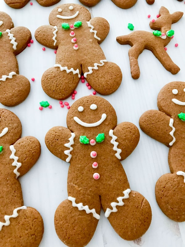A gingerbread man on a white table with white, green, and red icing