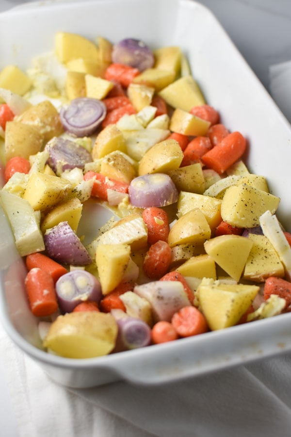 Carrots, potatoes, and shallots in a white baking dish prepared to be roasted