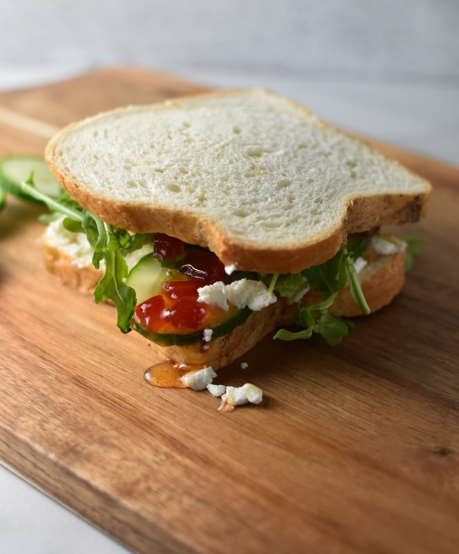 A goat cheese, chili jam, arugula, and cumber sandwich on a wooden cutting board