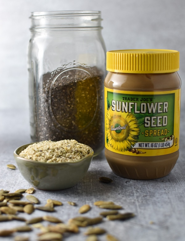 A mason jar with chia seeds next to sunflower seed butter and hemp seeds