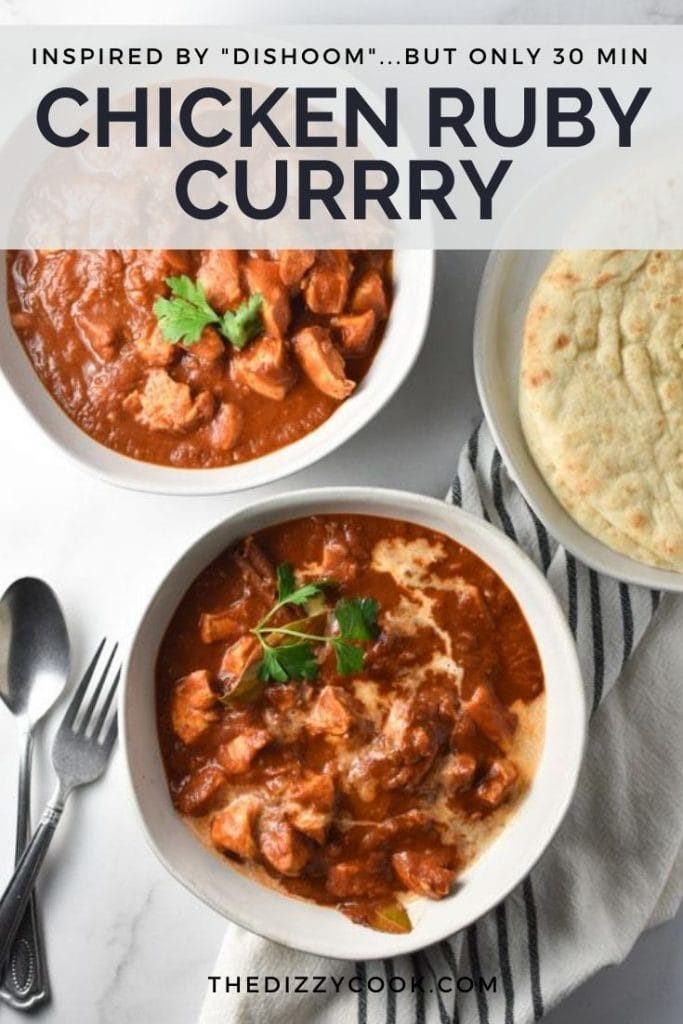 Two bowls of ruby curry next to naan bread