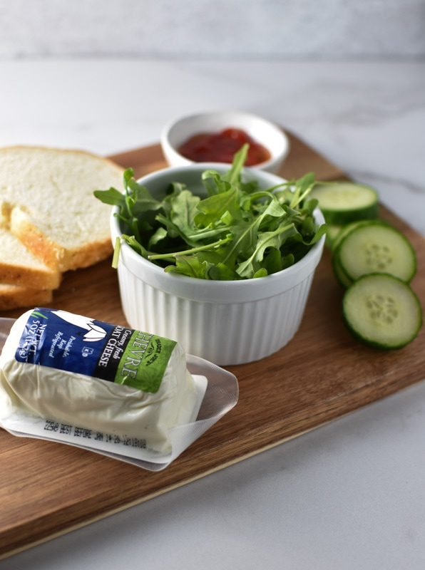 Goat cheese, bread, arugula, cucumber, and sweet chili sauce laid out on a wooden board as ingredients