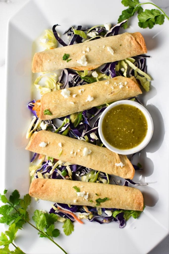 Baked creamy chicken taquitos on a white plate with slaw, cilantro, and salsa