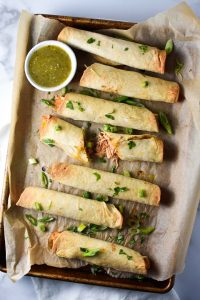 A sheet pan of baked creamy chicken taquitos, one broken to show the filling, topped with cilantro with salsa verde
