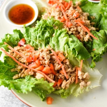Thai Chicken Lettuce Wraps on a plate topped with carrots, peppers, and a sauce on the side