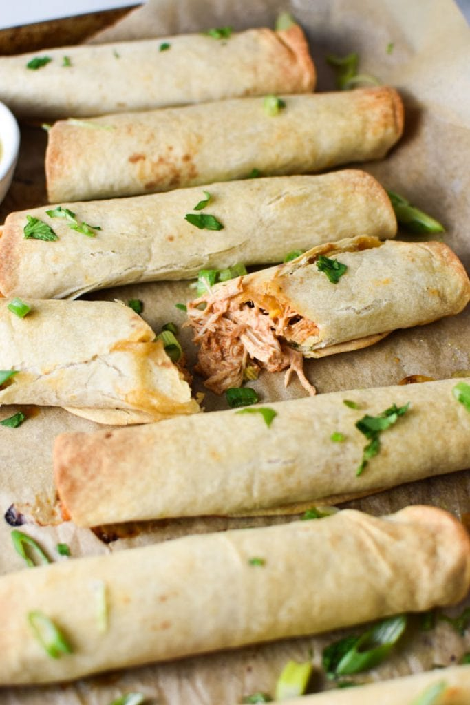 A sheet pan of baked creamy chicken taquitos topped with cilantro and green onion