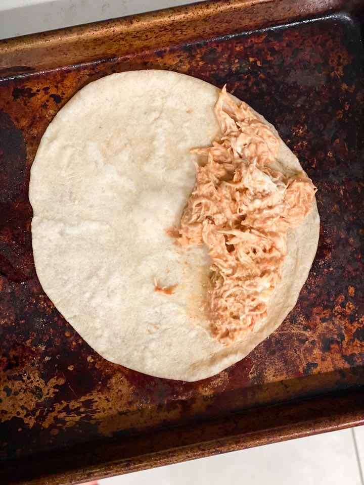 Creamy chicken taquito filling in one side of a tortilla on a baking sheet