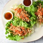 Lettuce wraps with chicken on a plate next to two dipping sauces