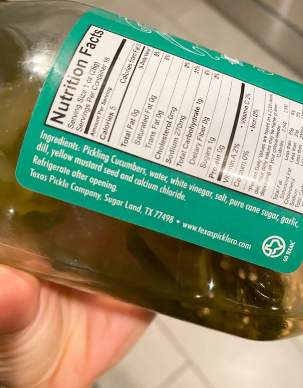 A jar of pickles with the ingredients showing