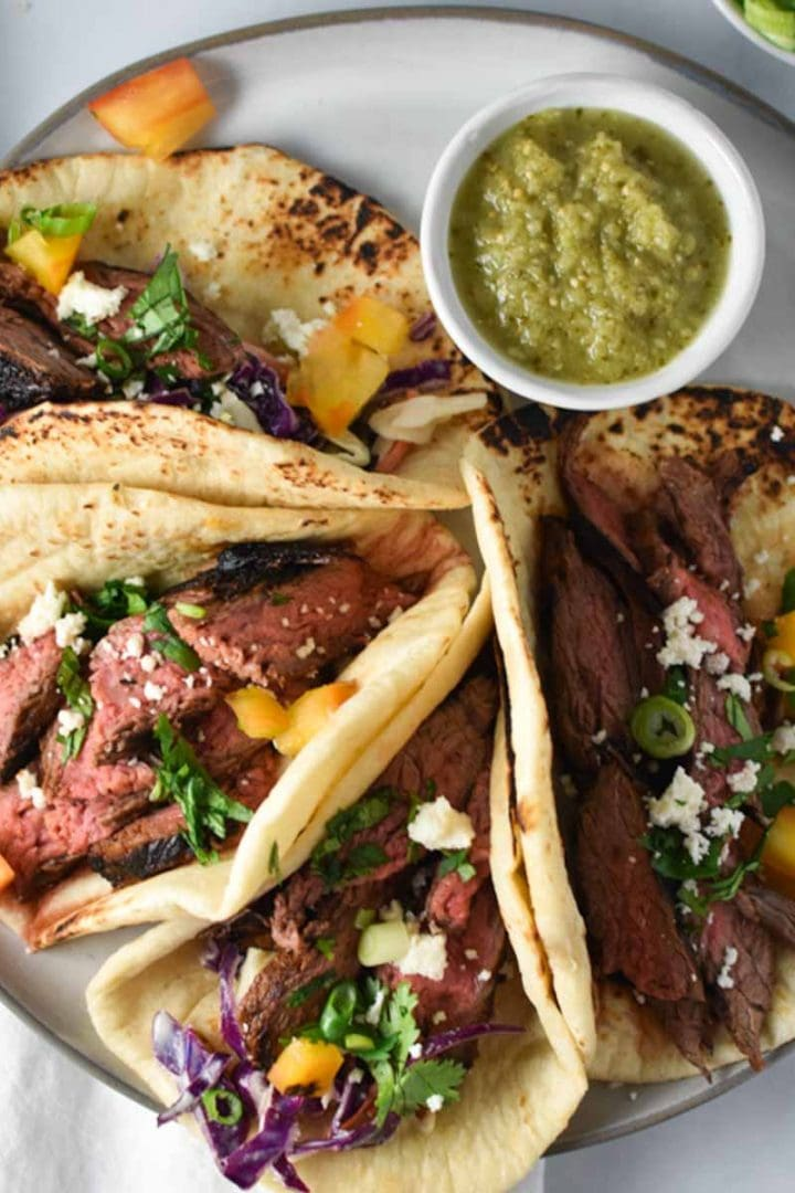 Grilled flank steak tacos lined up on a grey plate topped with cilantro and salsa verde