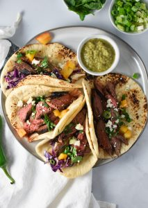 Steak tacos on a grey plate with salsa verde