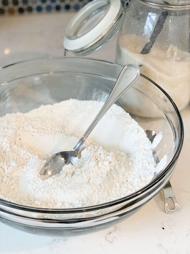 Flour, salt, and baking soda in a glass bowl being mixed with a spoon