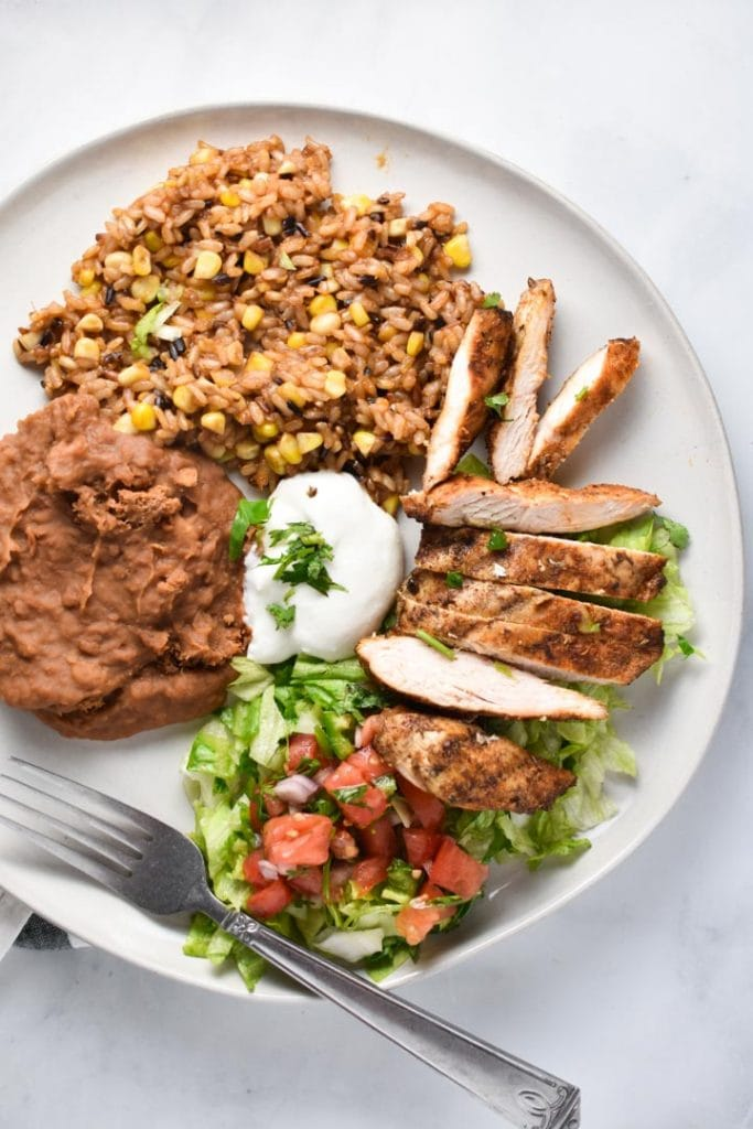 Mexican grilled chicken on a plate with beans, rice, lettuce, tomatoes, and cilantro