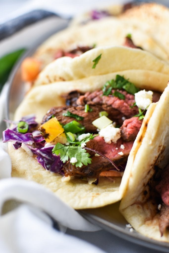 A taco with grilled steak, cilantro, and cheese