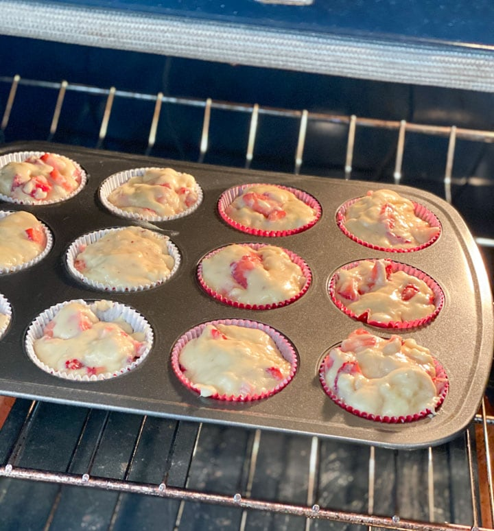 Unbaked strawberry muffins in an oven