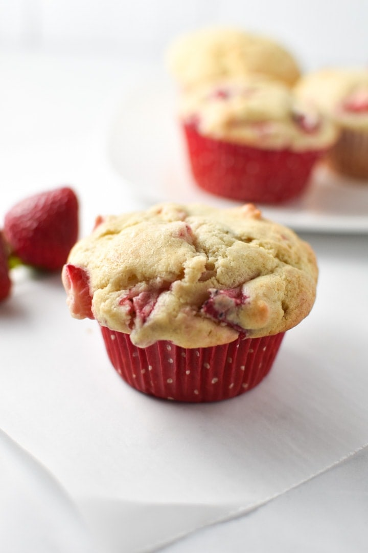 A strawberry cream cheese muffin on parchment paper with strawberries