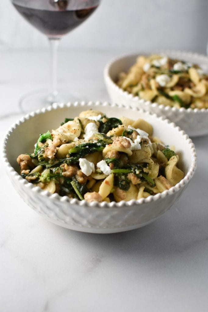 Orecchiette with broccoli rabe and sausage in a while bowl next to a wine glass