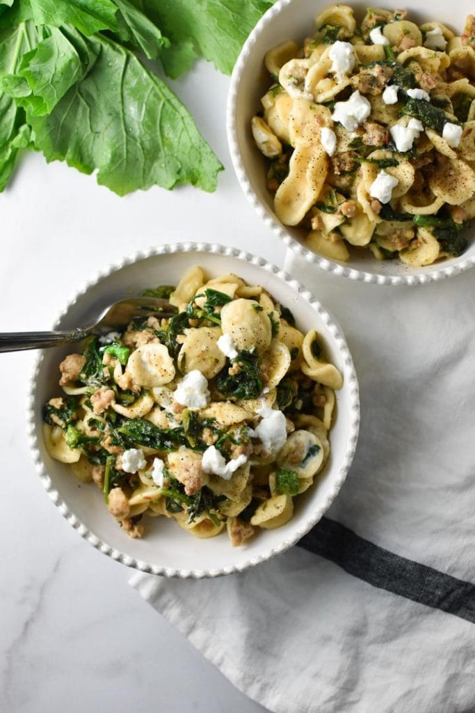 Two bowls of pasta with greens on the table next to a striped napkin with a fork
