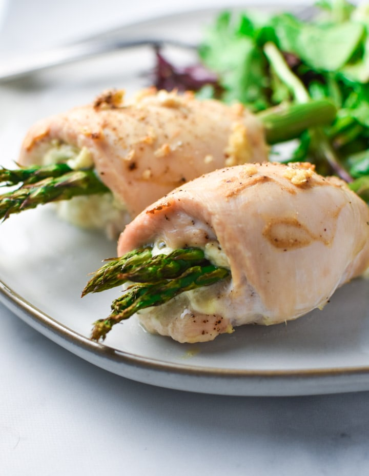 2 rolled chicken breasts stuffed with boursin cheese and asparagus on a plate