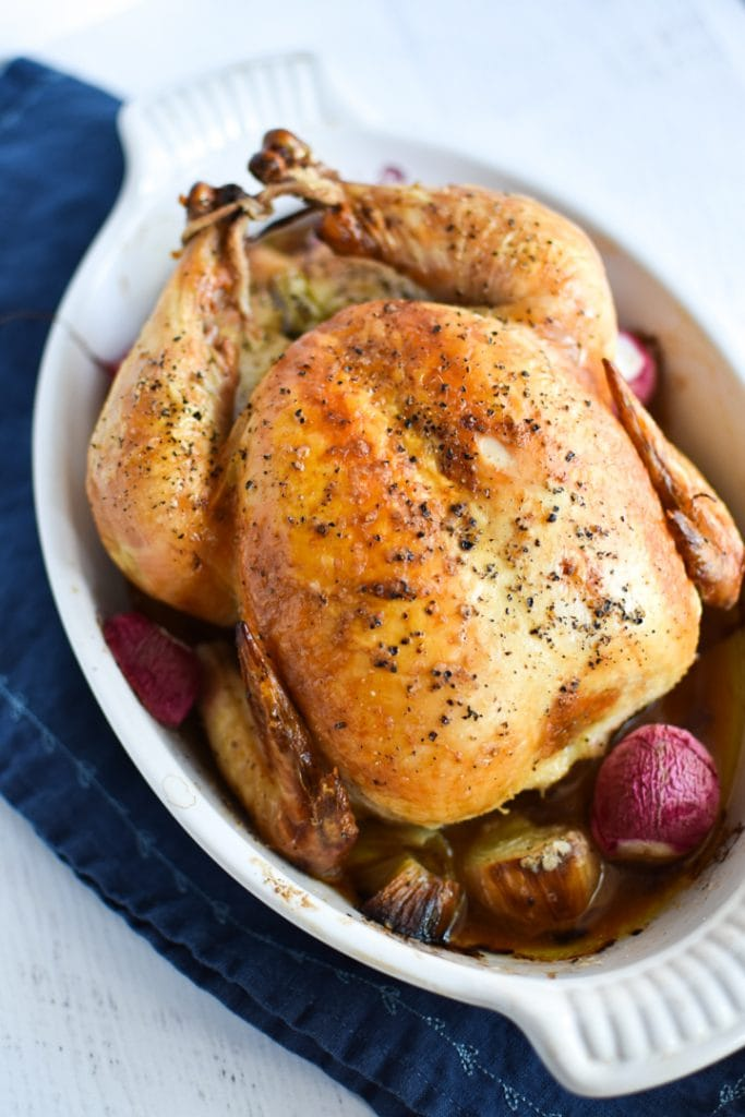 A whole roasted chicken in a white dish