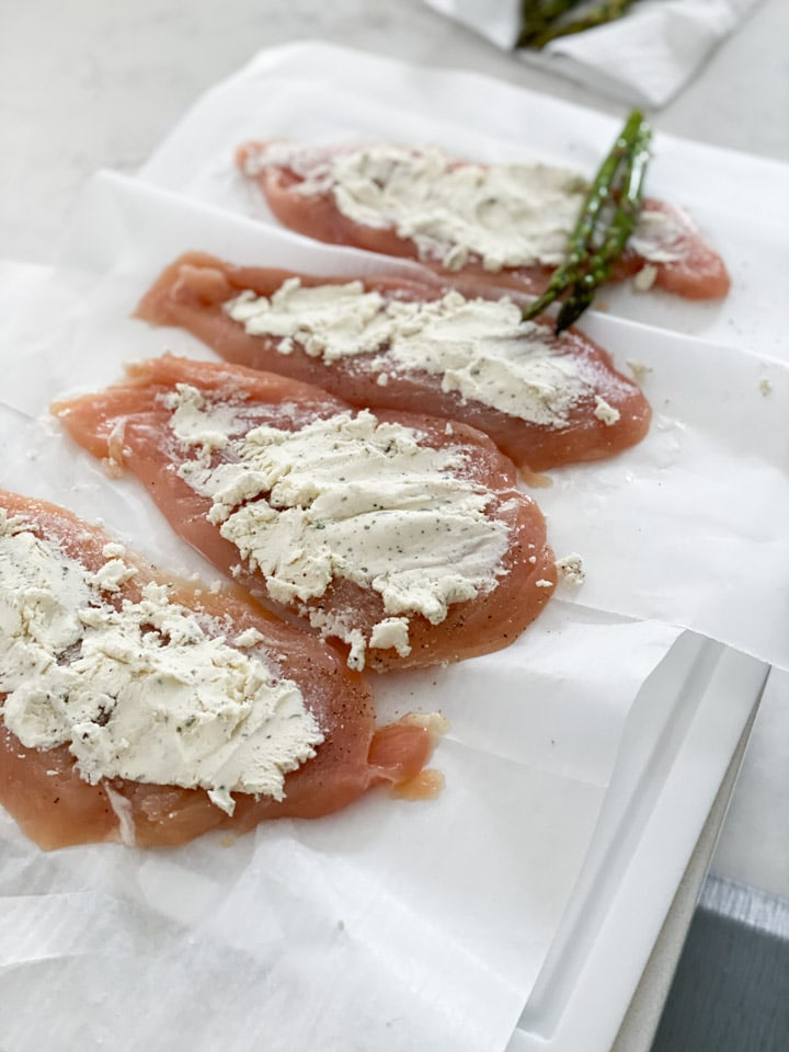 Boursin cheese spread on raw chicken breasts lined up in a row