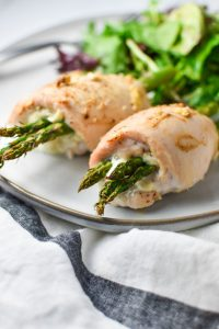 Two cheese stuffed chicken breast roll ups on a plate