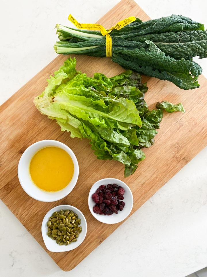 Ingredients for a kale salad on a cutting board